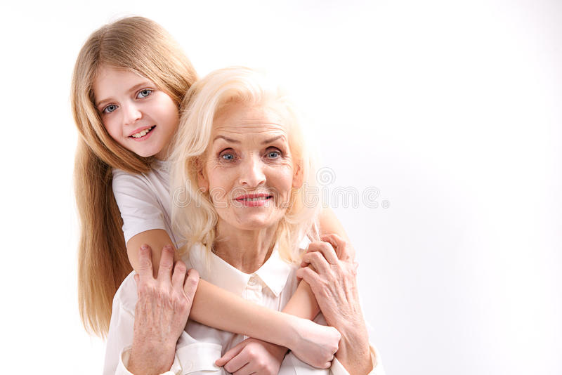 Small girl embracing old woman. Young grandchild is hugging her grandmother. They are looking at camera with smile. . Portrait and copy space royalty free stock image