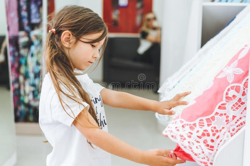 Girl in a fabric store chooses a multi-colored fabric stock photo