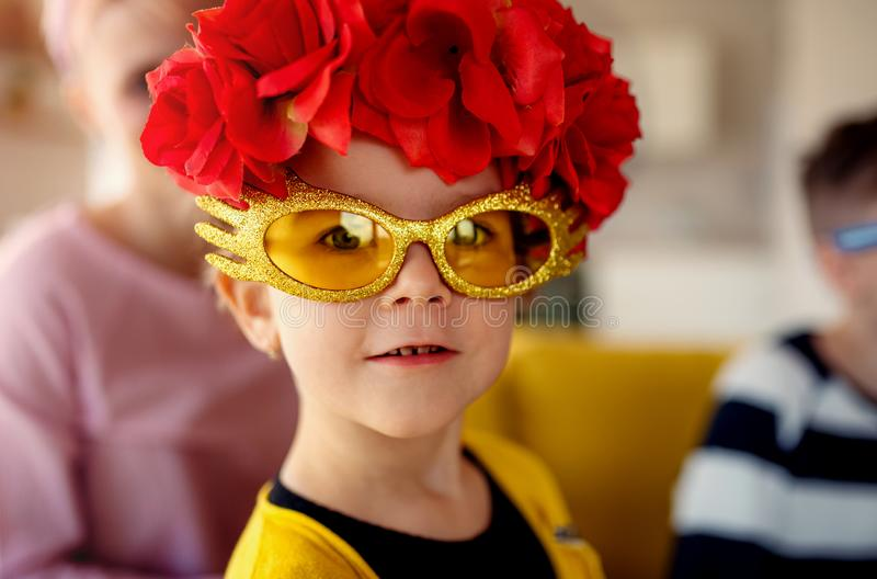 A small girl with family having fun at home, wearing party glasses. stock photo