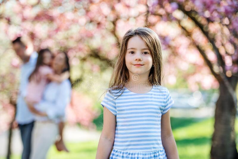 A small girl with family outside in spring nature, looking at camera. stock photo