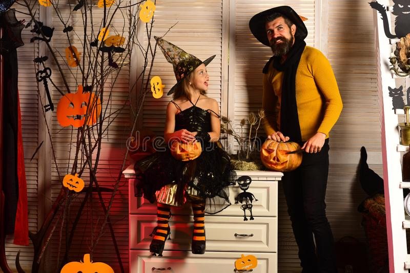 Small girl and father carve pumpkins for halloween. Happy family celebrate halloween. Small girl and father prepare for stock photos