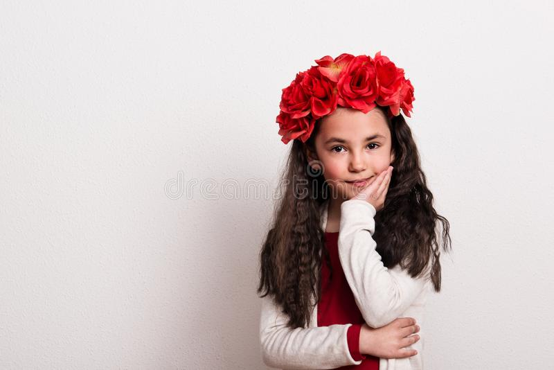 A small girl with flower headband standing in a studio, chin resting on her hand. stock images