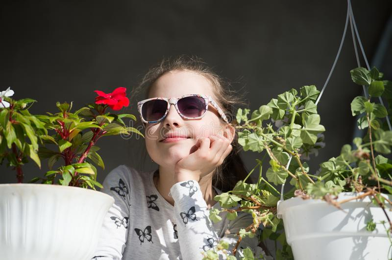 Small girl with flowers. Fashion child wear sunglasses on sunny day. Beauty kid with plant pots in summer or spring. Freshness and royalty free stock image