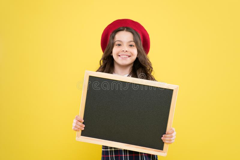 Small girl in french beret. advertisement. child with empty blackboard. parisian child on yellow background. happy girl. With curly hair in beret. your stock photography