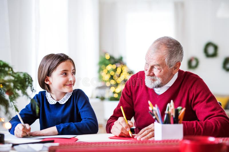 A small girl and her grandfather writing Christmas cards together. royalty free stock photo