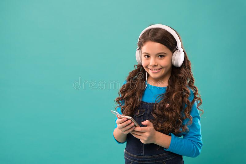 Small girl hold mp3 player. choosing favorite song. e-learning in modern life. schoolgirl use new technology. copy space. Kid listen music in headphones. small stock photography
