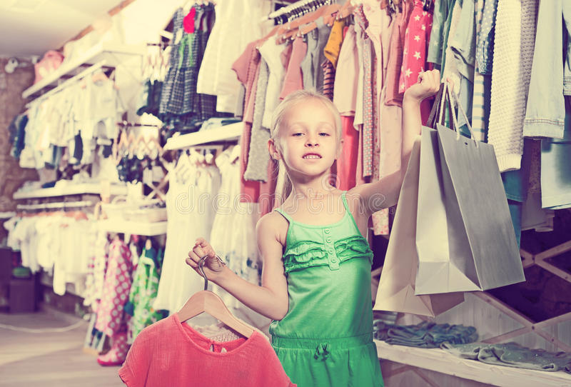 Small girl holding bags in children boutique stock photo