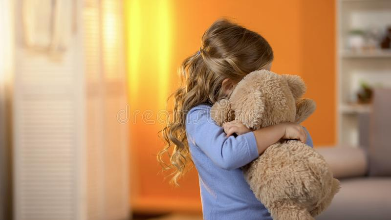 Small girl hugging teddy bear, problems with socialization, lack of friends stock image