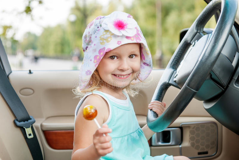 Small girl iseats at steering wheel royalty free stock photos