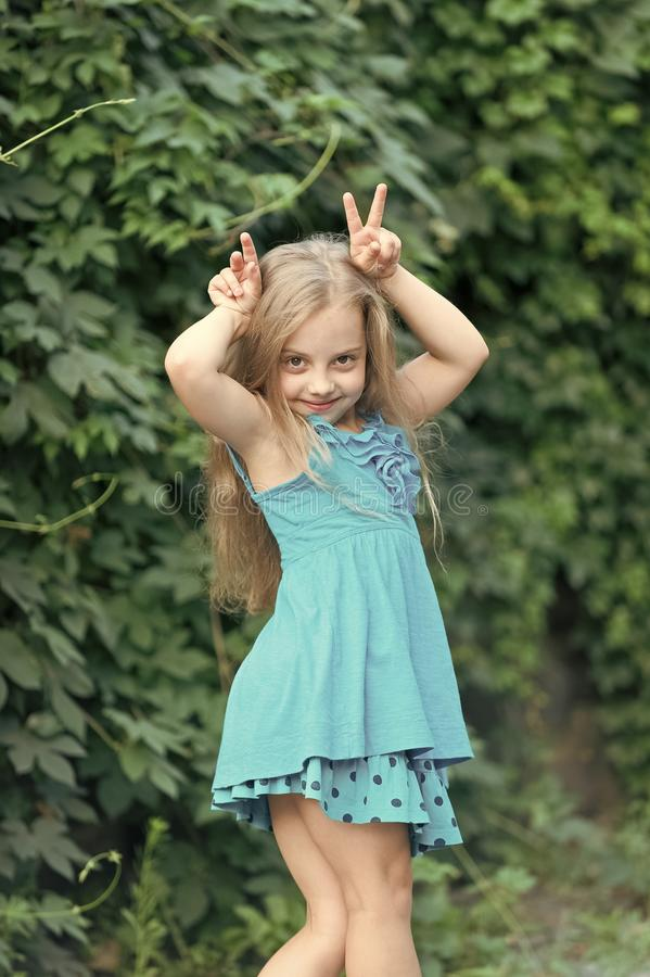Small girl with long hair smile with horns hands, beauty. Happy child in summer dress on natural landscape, fashion. Beauty, fashion, hairstyle royalty free stock photo