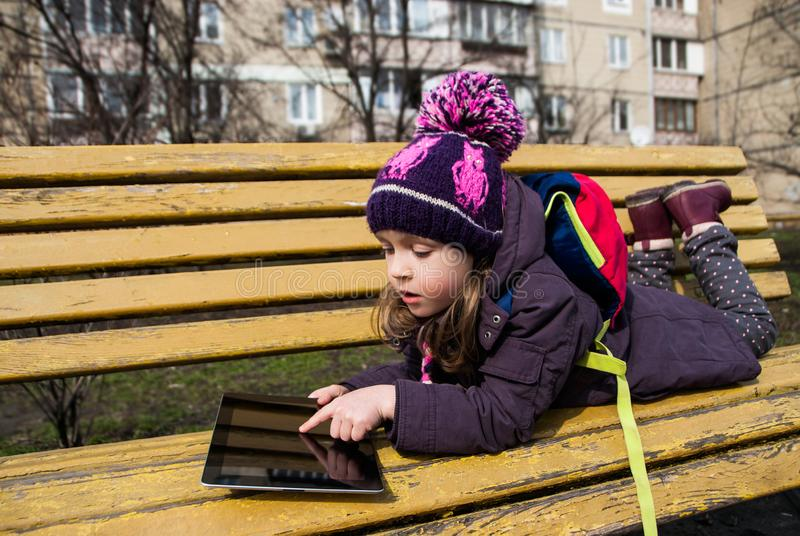 Small girl is lying on a bench outdoors and touches digital tablet by finger royalty free stock photography