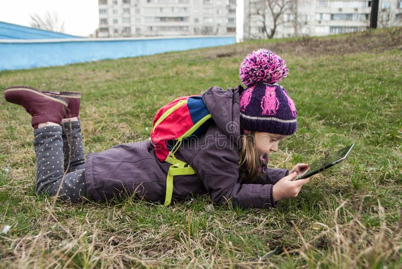 Small girl lying on the grass and watching cartoons, urban lifestyle stock photos