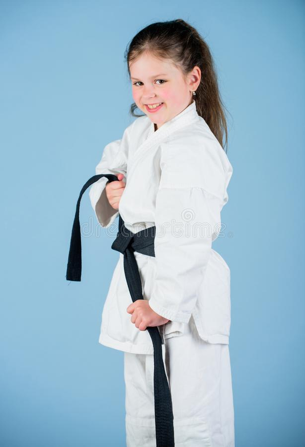 Small girl in martial arts uniform. little girl in gi sportswear. practicing Kung Fu. happy childhood. knockout. energy. And activity for kids. sport success in stock photo