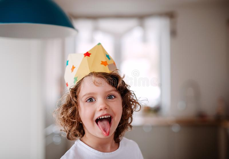 A small girl with a paper crown at home, having fun when looking at camera. stock photos