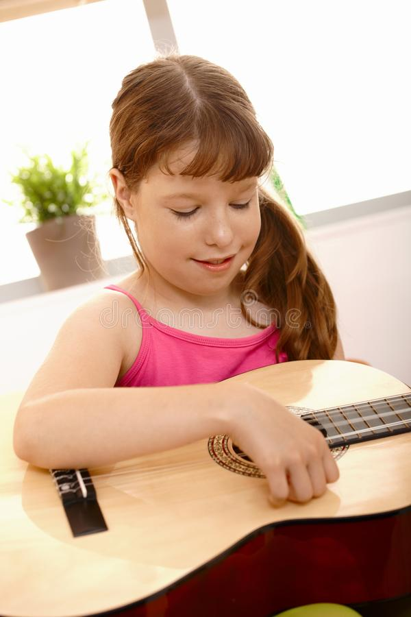 Small girl playing guitar stock image