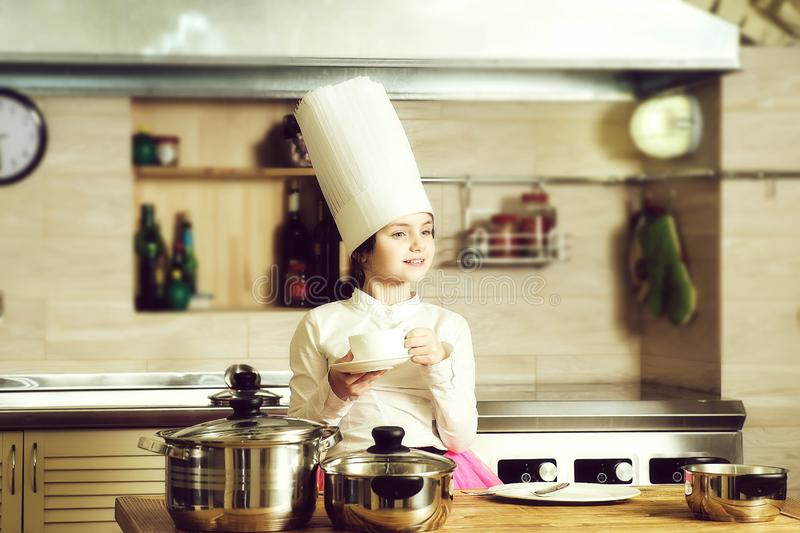 Little girl cook. Small girl with pots and spoons in cook hat and pink skirt in kitchen royalty free stock images