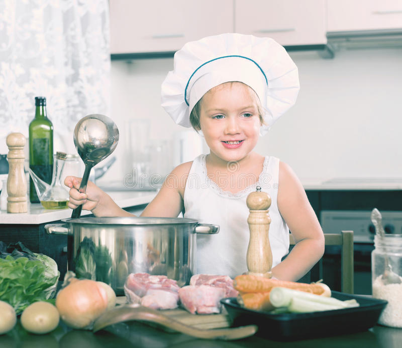 Small girl preparing soup with vegetables royalty free stock photos