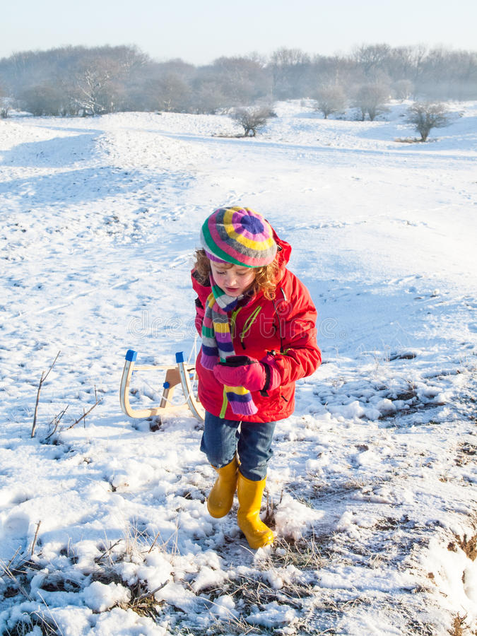 Small girl pulling a sledge stock image