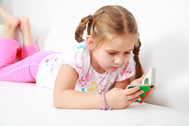 Small girl relaxing and reading royalty free stock photos