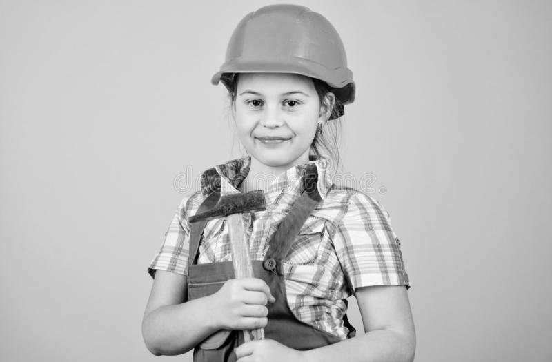 Small girl repairing with hammer in workshop. Child care development. Future profession. Builder engineer architect. Kid. Worker in hard hat. Tools to improve stock photos