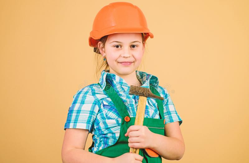 Small girl repairing with hammer in workshop. Child care development. Future profession. Builder engineer architect. Kid. Worker in hard hat. Tools to improve royalty free stock images