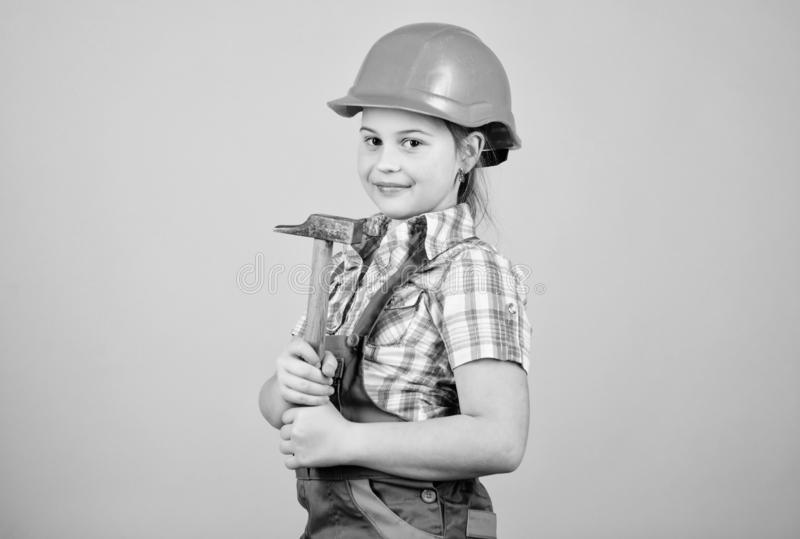 Small girl repairing with hammer in workshop. Tools to improve yourself. Repair. Child care development. Future. Profession. Builder engineer architect. Kid royalty free stock images