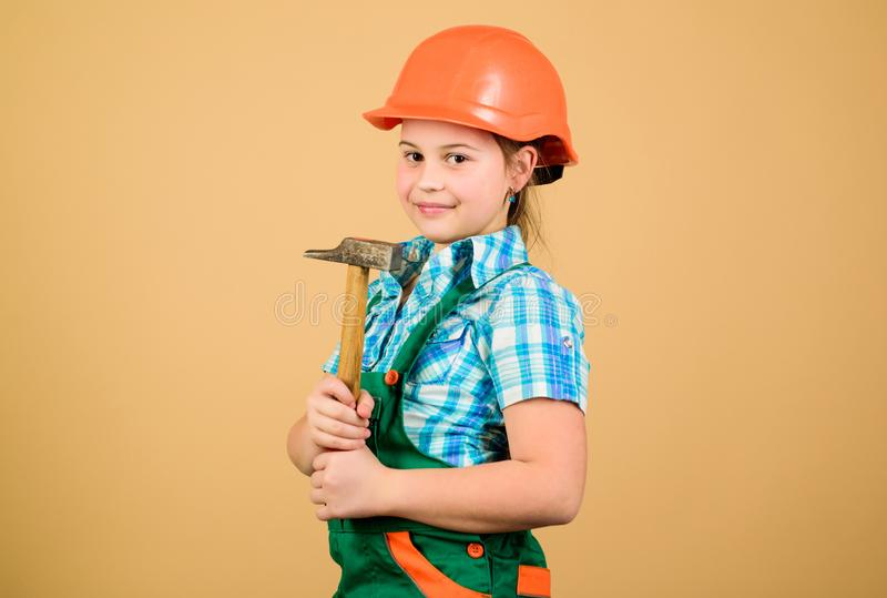 Small girl repairing with hammer in workshop. Tools to improve yourself. Repair. Child care development. Future. Profession. Builder engineer architect. Kid stock photography