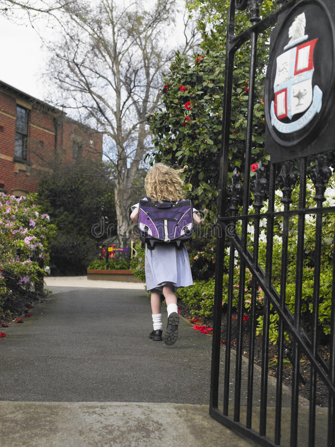 Small Girl Running Out Of The School Gate stock photography