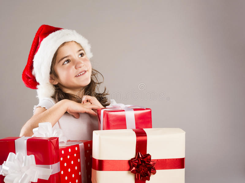 Small girl in santa hat with christmas gift stock photos