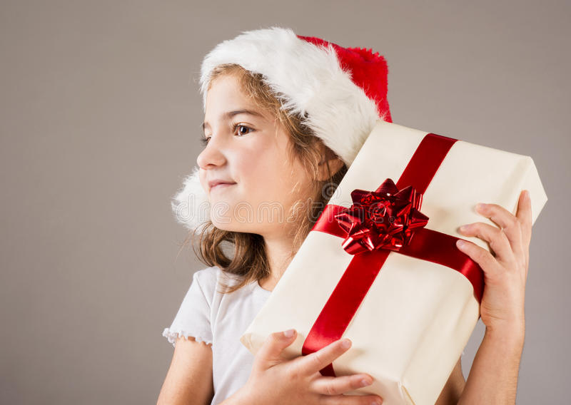 Small girl in santa hat with christmas gift royalty free stock images