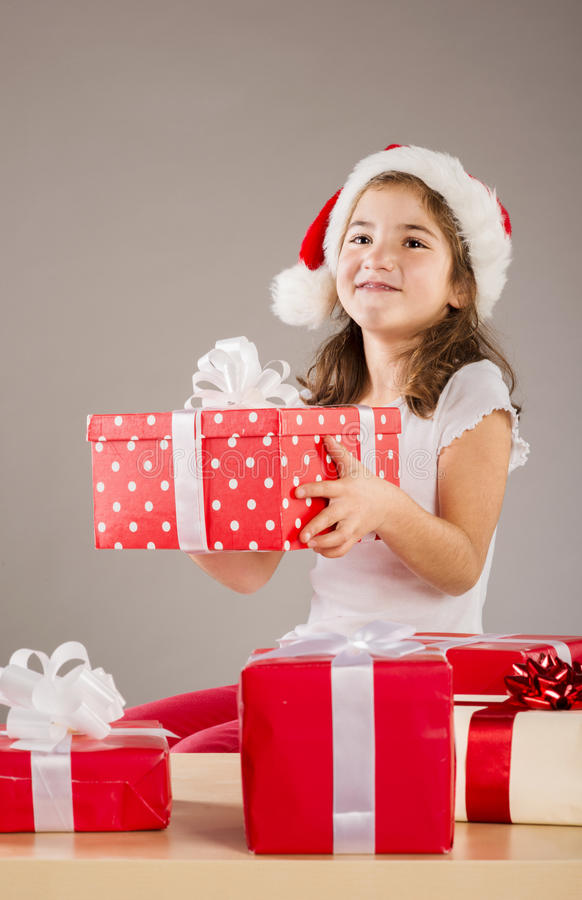 Small girl in santa hat with christmas gift stock images