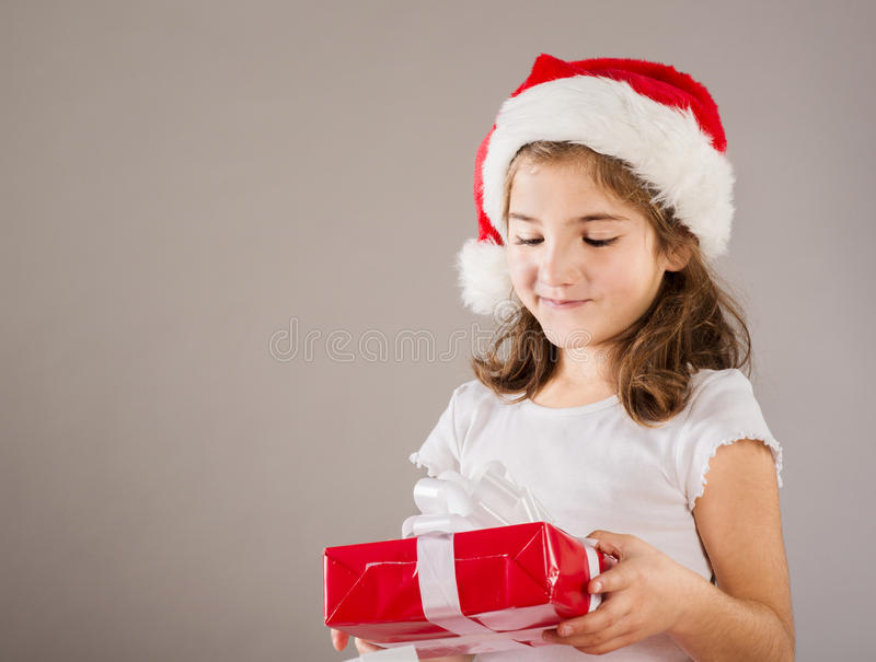 Small girl in santa hat with christmas gift royalty free stock photo