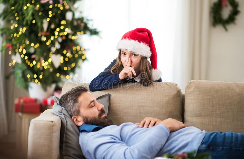 A small girl doesn`t want to wake up her sleeping father at Christmas time. stock image
