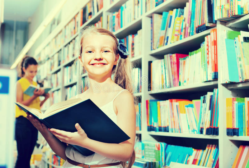 Small girl in school age standing with open book. Cute blond glad girl in school age standing with open book in store royalty free stock photography