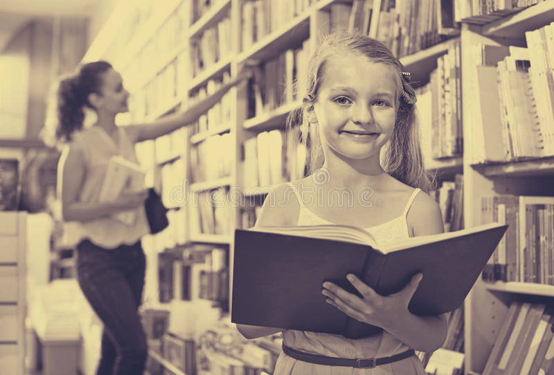 Small girl in school age standing with open book. Small cute blond girl in school age standing with open book in store stock image