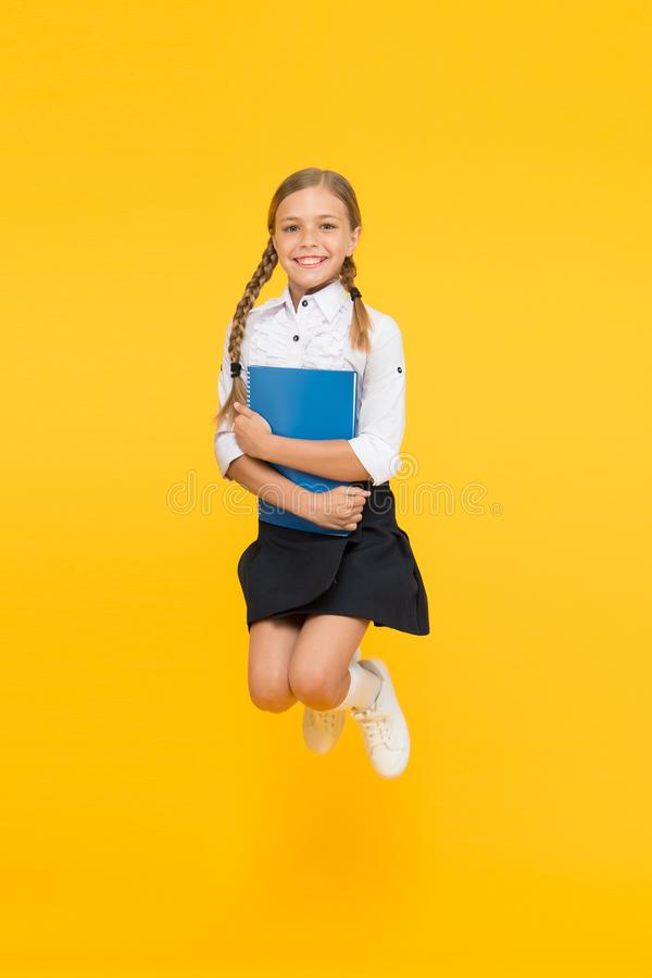 Small girl in school uniform. cheerful girl with workbook. Education. dictionary notebook. Get information. reading. Story. childrens literature. kid learning stock image