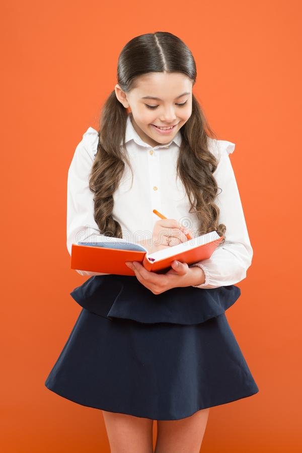 Small girl in school uniform. get information form book. back to school. Small girl with workbook for writing. Schoolgirl writing notes on orange background royalty free stock images