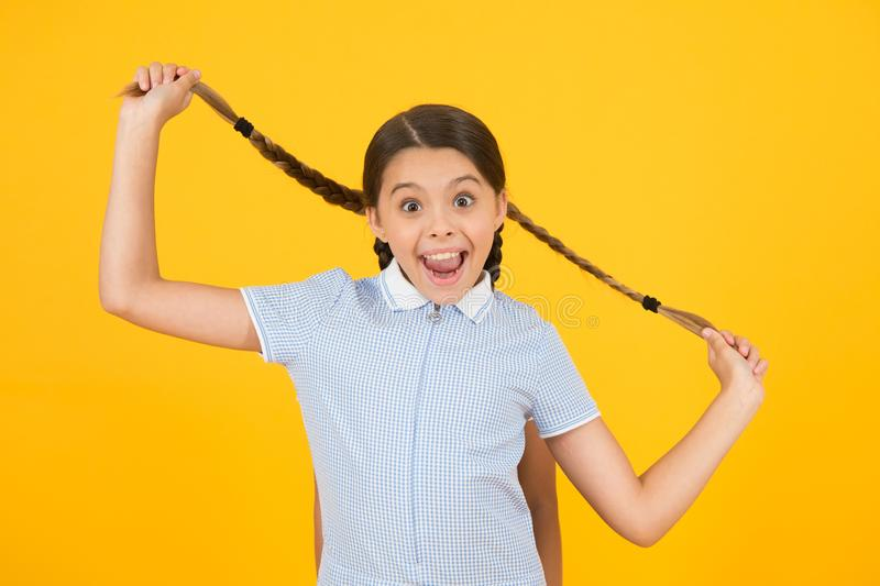 Small girl in school uniform. retro look. child hold pigtail of girl behind. old school. kid fashion. happy child on stock images