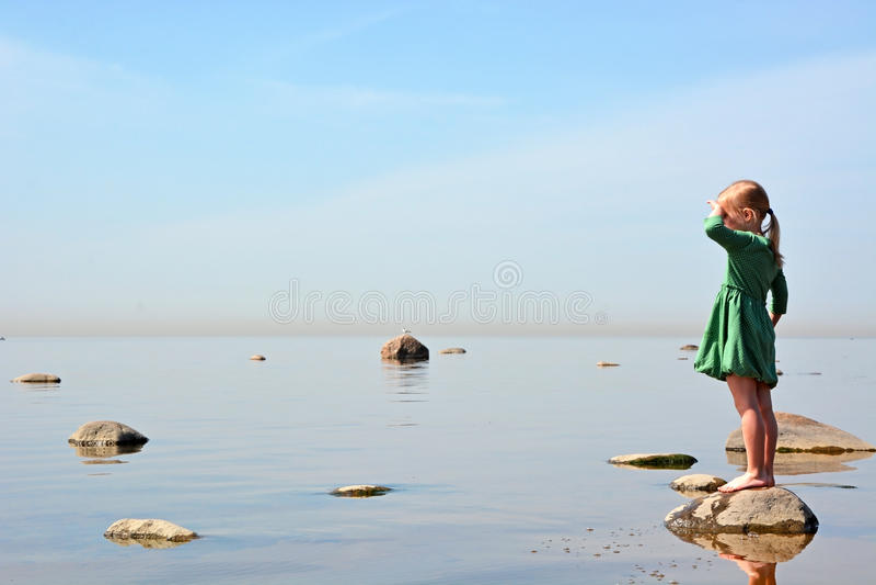 Small girl at the sea shore royalty free stock photography