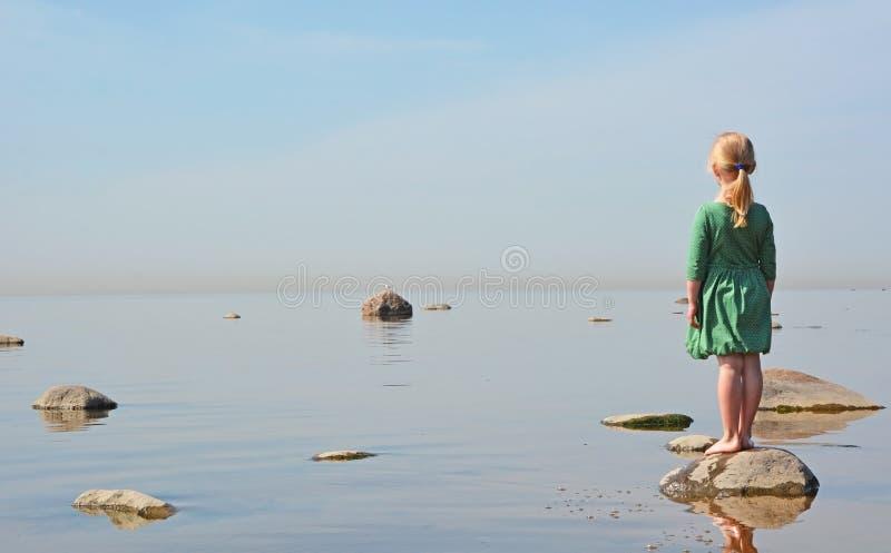 Small girl at the sea shore stock photos
