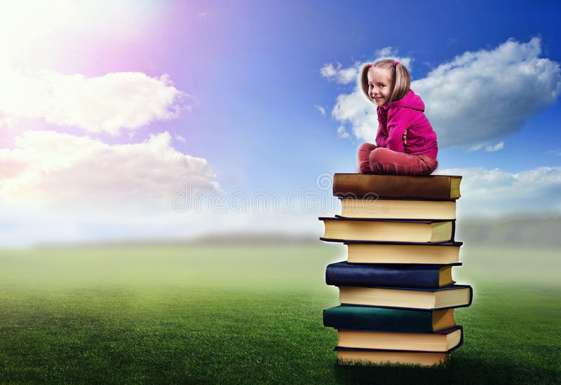Small girl sits on the pile of books royalty free stock photo