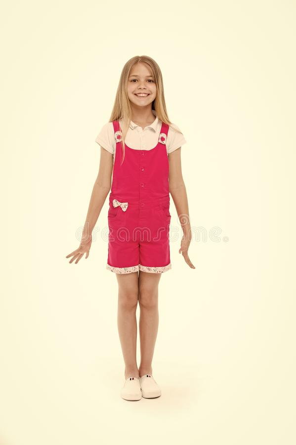 Small girl smile in pink jumpsuit isolated on white. Child smiling with long blond hair. Kid model in fashionable. Overall. Fashion style and trend. Happy royalty free stock photo