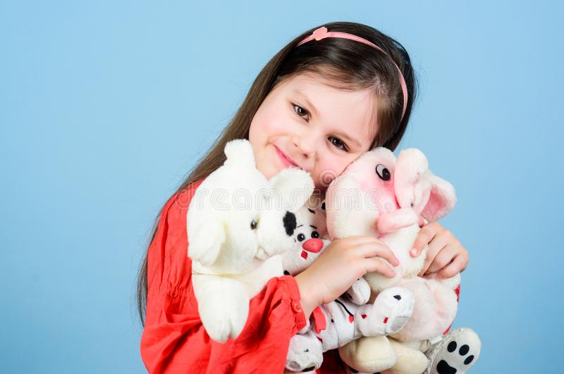 Small girl smiling face with favorite toys. Happy childhood. Little girl play with soft toy teddy bear. Sweet childhood stock image