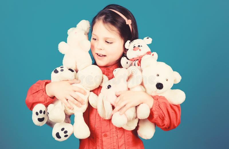 Small girl smiling face with toys. Happy childhood. Little girl play with soft toy teddy bear. Lot of toys in her hands stock photos