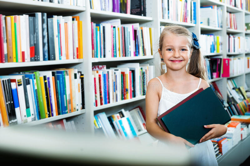 Small girl standing in book store and taking literature. Small smiling blond glad girl standing in book store and taking chosen literature royalty free stock photo