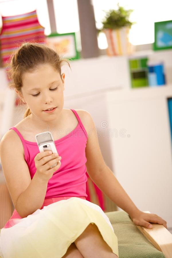 Small girl texting on phone at home stock photography