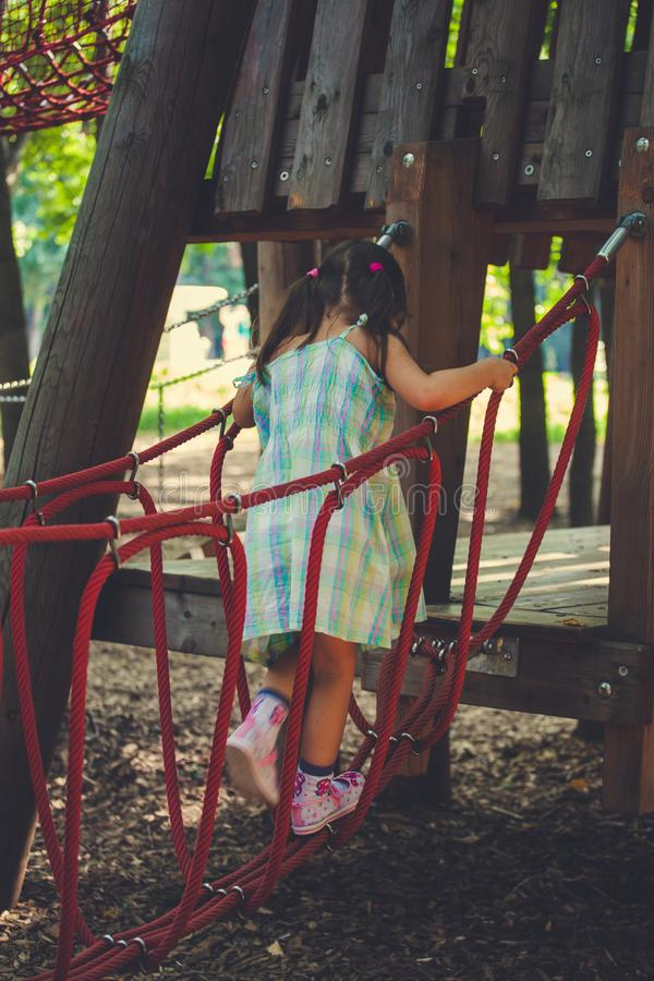 Small girl walking on a monkey bridge on a children`s playground royalty free stock photography
