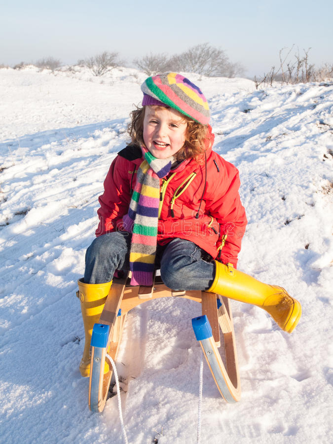 Small girl on a wooden sledge royalty free stock photo