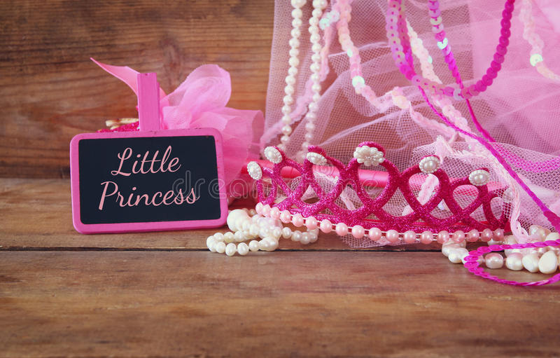 Small girls party outfit: crown and wand flowers next to small chalkboard with phrase LITTLE PRINCESS: on wooden table. Bridesmaid or fairy costume stock image