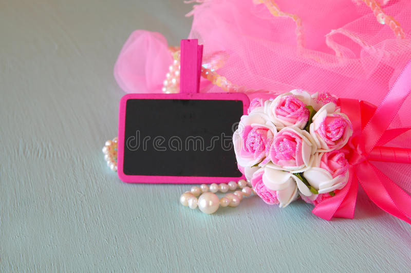 Small girls party outfit: crown and wand flowers next to small empty chalkboard on wooden table. bridesmaid or fairy costume.  stock images
